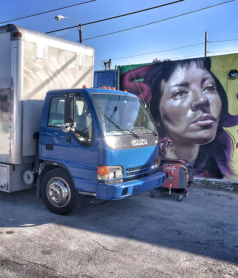 Grip truck in front of mural outdoors